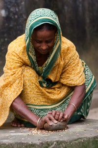 A woman in Bangladesh grinds maize to prepare food for her family