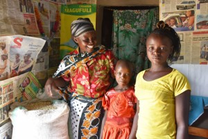 Valeria and her daughters and part of their bountiful maize harvest from 'ngamia' seed. Photographer: CIMMYT/Brenda Wawa